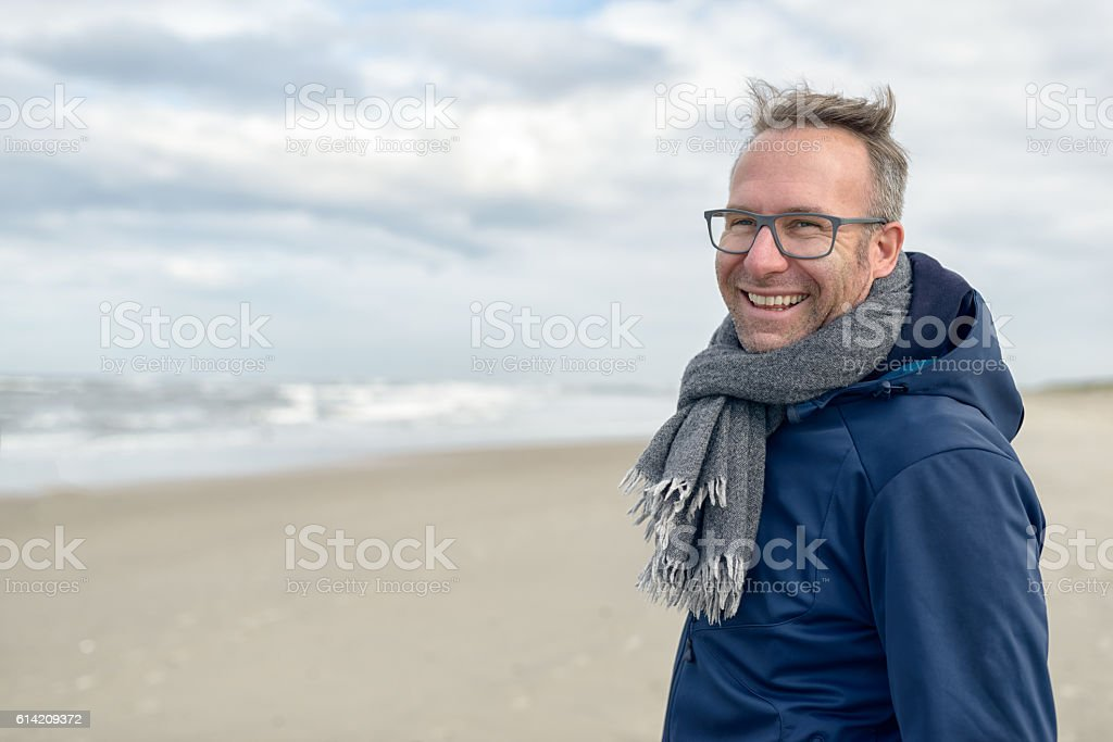 Smiling middle-aged man on an autumn beach stock photo