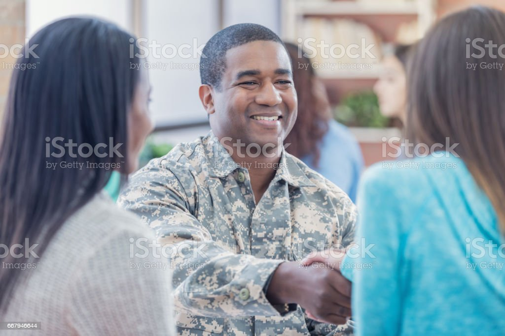 Smiling military recruiter greets students at recruitment event stock photo