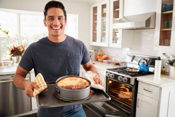 Smiling millennial Hispanic man standing in kitchen presenting the cake he has baked to camera Smiling millennial Hispanic man standing in kitchen presenting the cake he has baked to camera making a cake stock pictures, royalty-free photos & images