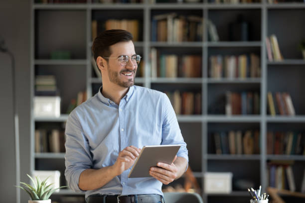 Smiling millennial man use table thinking at workplace stock photo