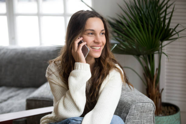 Smiling millennial mestizo woman talking on the phone at home Smiling millennial mestizo woman talking on the phone at home, happy young girl holds cellphone making answering call, attractive teenager having pleasant conversation chatting by mobile with friend bingo caller stock pictures, royalty-free photos & images
