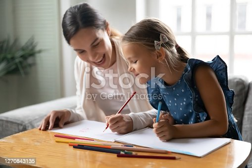 Smiling millennial mother or older sister enjoying drawing pictures with small child girl in paper album, spending weekend hobby time together at home, sitting at table, creative skills development.