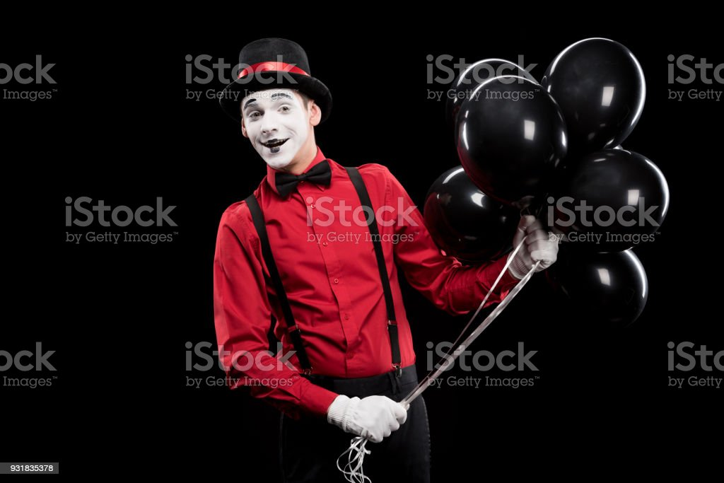 smiling mime holding bundle of black balloons isolated on black stock photo
