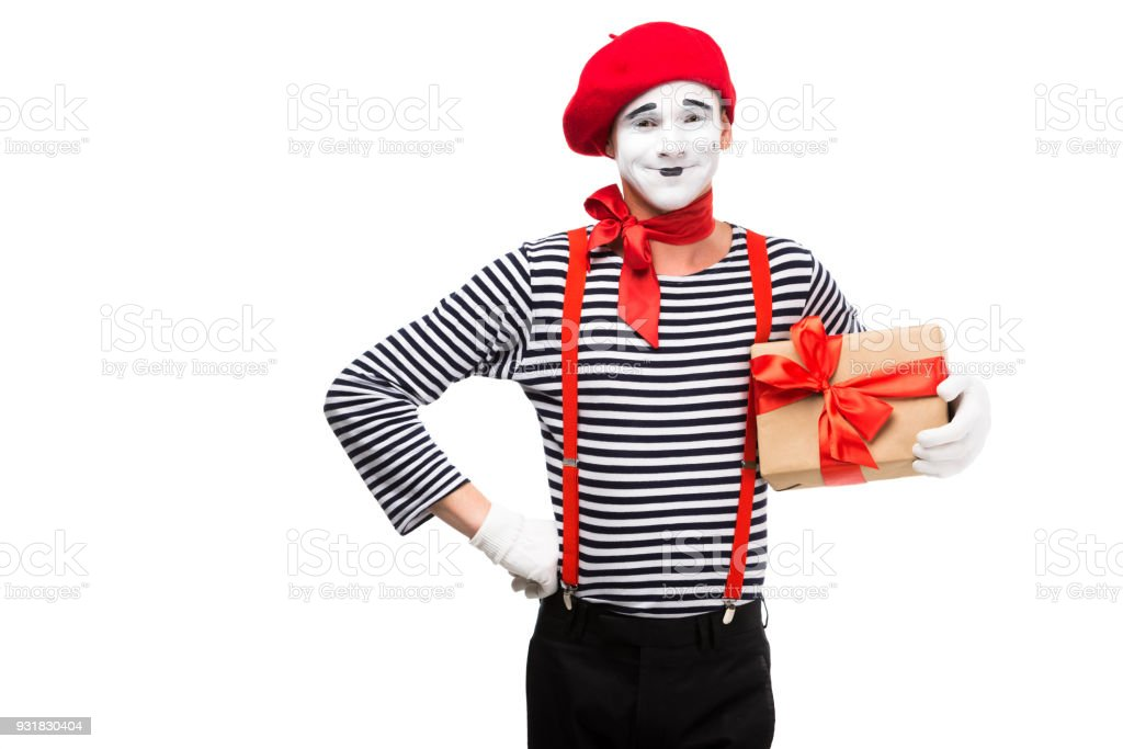 smiling mime holding present box and looking at camera isolated on white stock photo