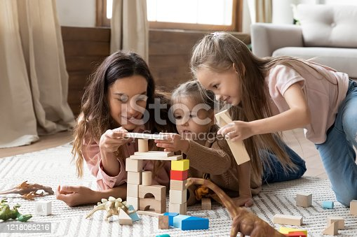 1063760138 istock photo Smiling mixed race babysitter playing with children. 1218085216