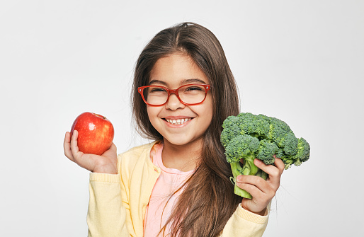 Smiling mixed race girl holding an apple and broccoli in her hands. Healthy vegetarian food for kids