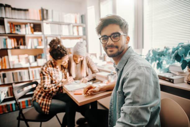 lächelnde gemischte rasse männliche student sitzen am schreibtisch, schauen auf kamera und studieren für prüfungen. im hintergrund seine freunde studieren. bibliotheksraum. - öffentliches gebäude stock-fotos und bilder