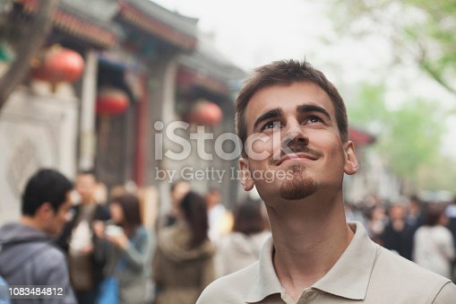 Smiling mixed race man looking up outdoors