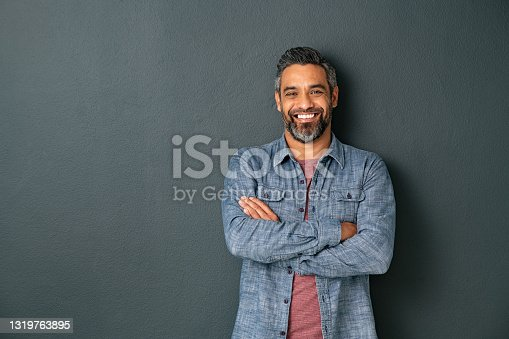 istock Smiling mixed race mature man on grey background 1319763895