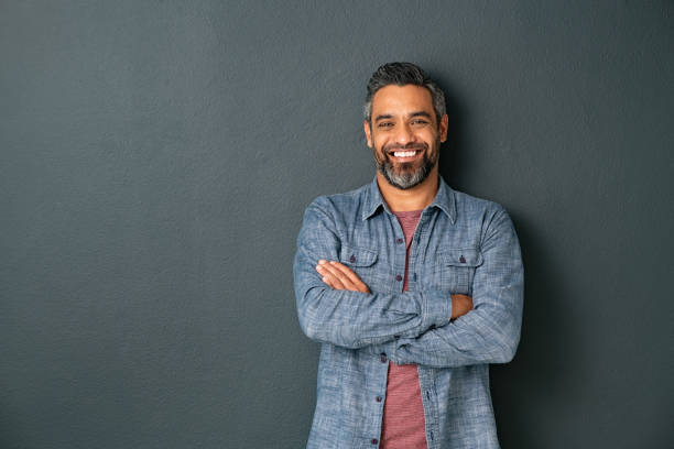 Smiling mixed race mature man on grey background stock photo