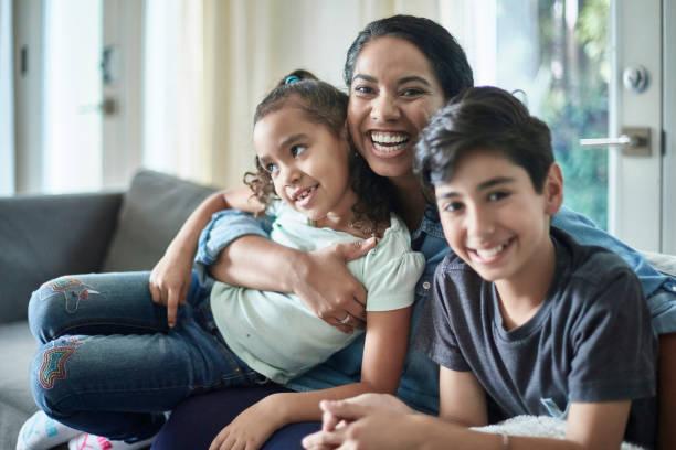 Lächelnde Mixed Race Mutter mit kleinen Kindern auf dem Sofa – Foto