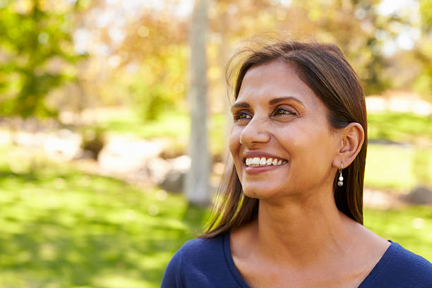 Smiling mixed race woman in park looking away from camera Smiling mixed race woman in park looking away from camera looking away stock pictures, royalty-free photos & images