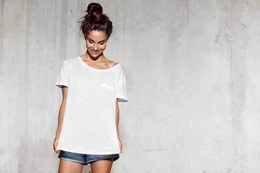 Smiling model in mock-up white shirt for design print.