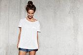 istock Smiling model in mock-up white shirt for design print. 1169982382