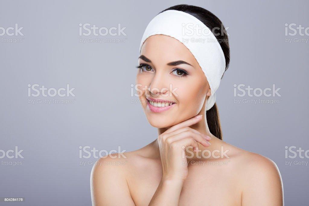 Smiling model with white headband touching chin stock photo