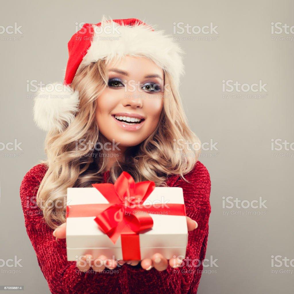 Sonriendo el modelo de mujer con sombrero de Santa y celebración de Navidad  sobre fondo con 7bb1233c471