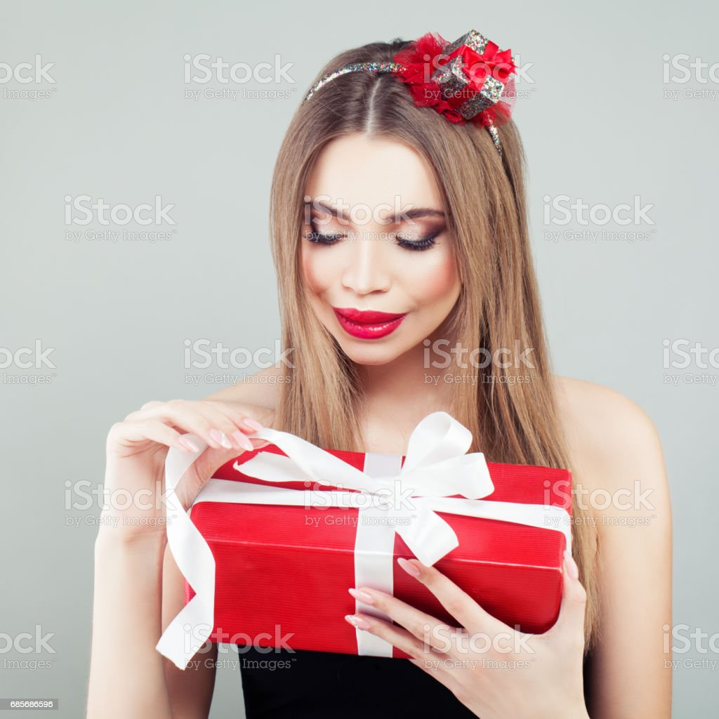 Smiling Model Woman with Makeup and Long Hair Holding Gift on Grey Background royalty-free stock photo