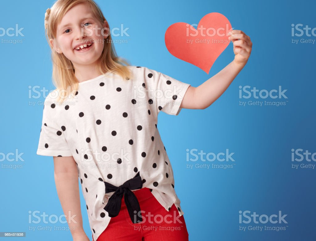 smiling modern child in red pants on blue showing paper heart royalty-free stock photo