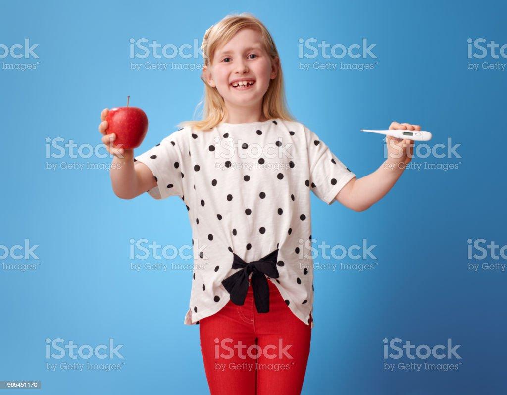 lächelnde moderne Kind zeigt einen Apfel und Thermometer auf blau - Lizenzfrei Abnehmen Stock-Foto