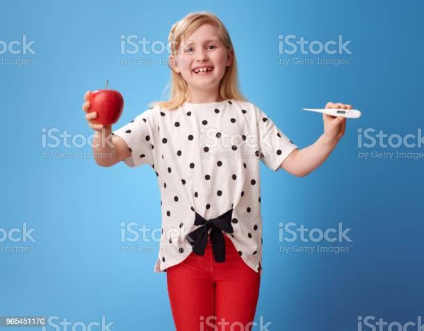Lächelnde Moderne Kind Zeigt Einen Apfel Und Thermometer Auf Blau Stockfoto und mehr Bilder von Abnehmen