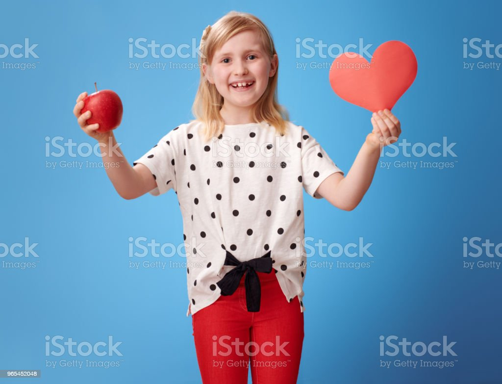 smiling modern child showing paper heart and an apple on blue royalty-free stock photo