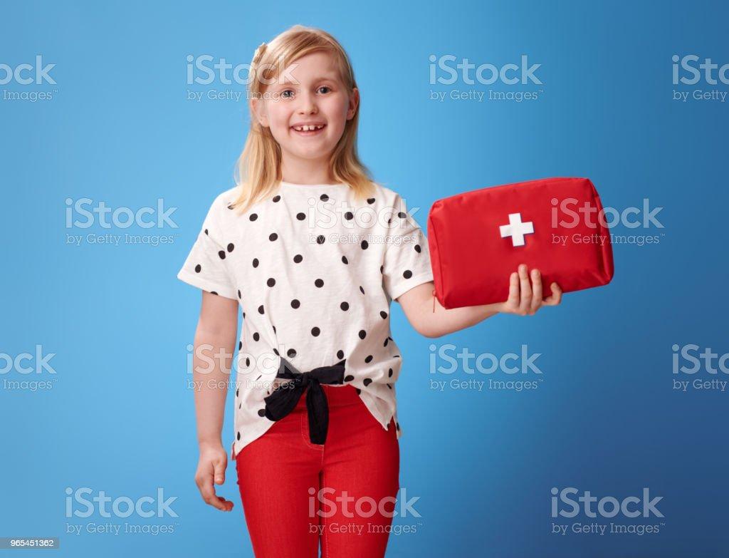 微笑的現代女孩在紅色褲子藍色顯示急救箱 - 免版稅一個人圖庫照片