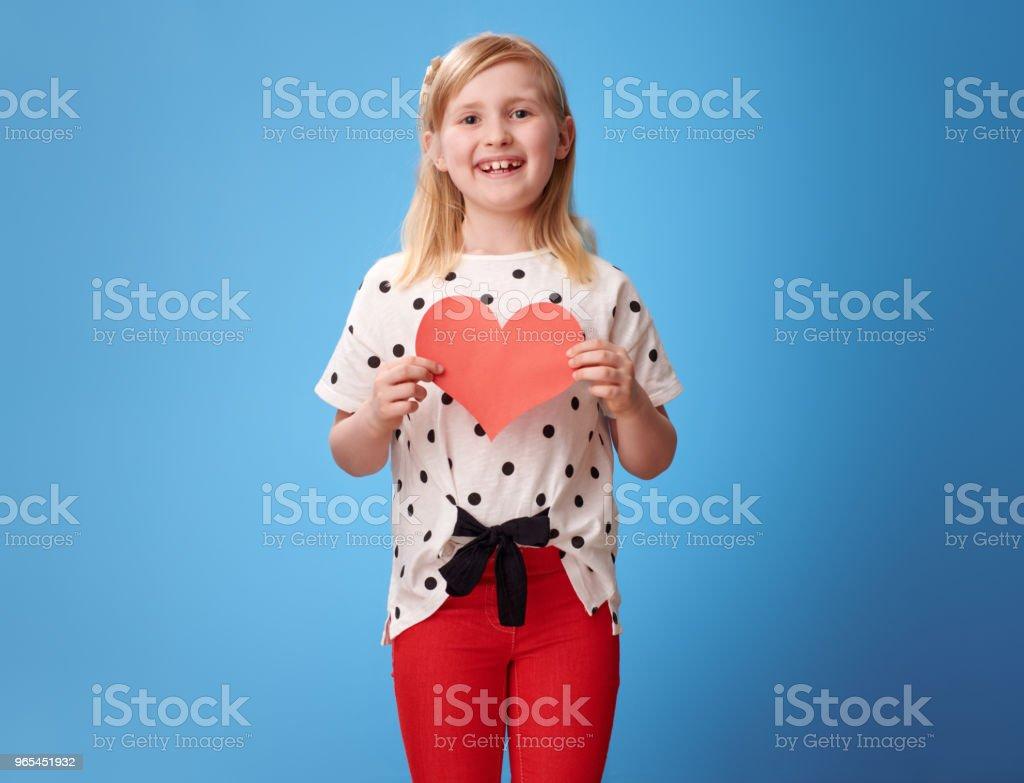 jeune fille moderne souriante dans un pantalon rouge sur bleu montrant le coeur de papier - Photo de Bleu libre de droits