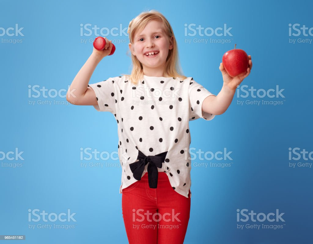 smiling modern girl showing biceps and an apple on blue zbiór zdjęć royalty-free