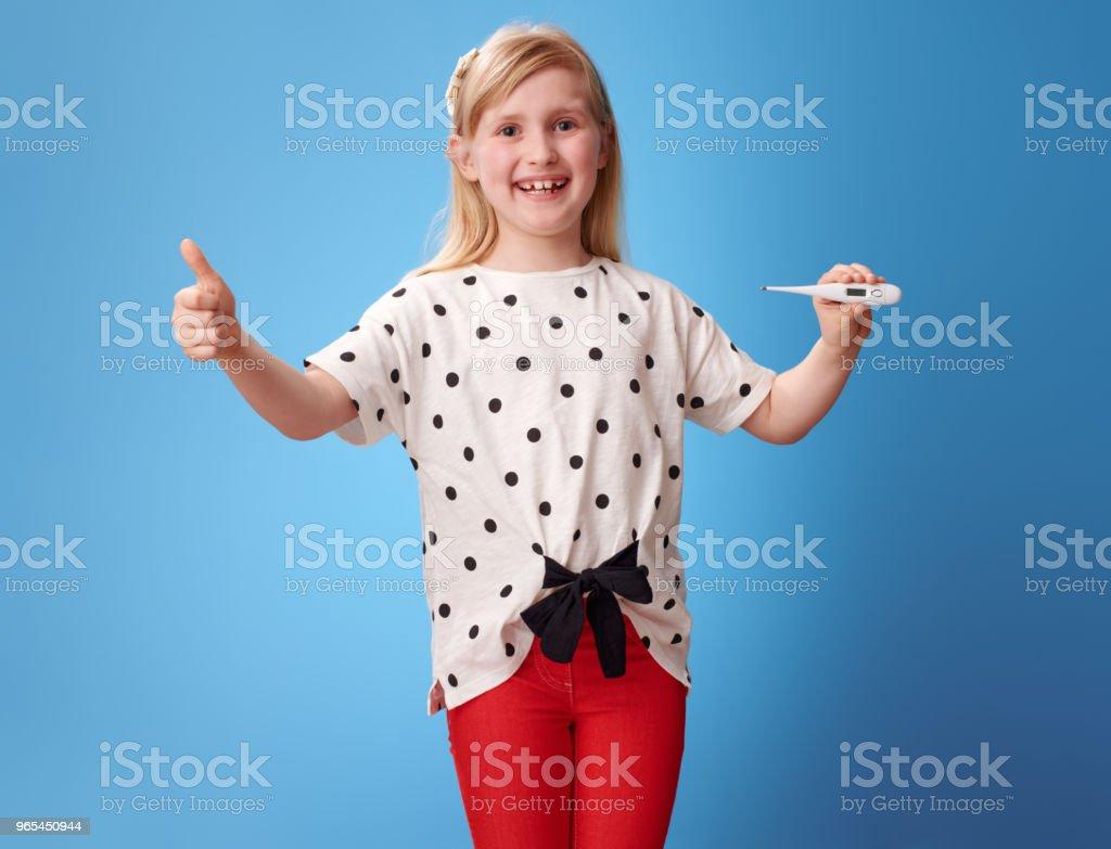微笑的現代女孩顯示大拇指和溫度計在藍色 - 免版稅一個人圖庫照片