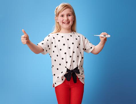 微笑的現代女孩顯示大拇指和溫度計在藍色 照片檔及更多 一個人 照片