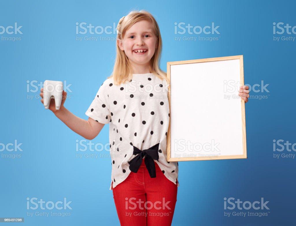 lächelnd, modernes Mädchen zeigen Zahn und leere Plakat auf blau - Lizenzfrei Blau Stock-Foto