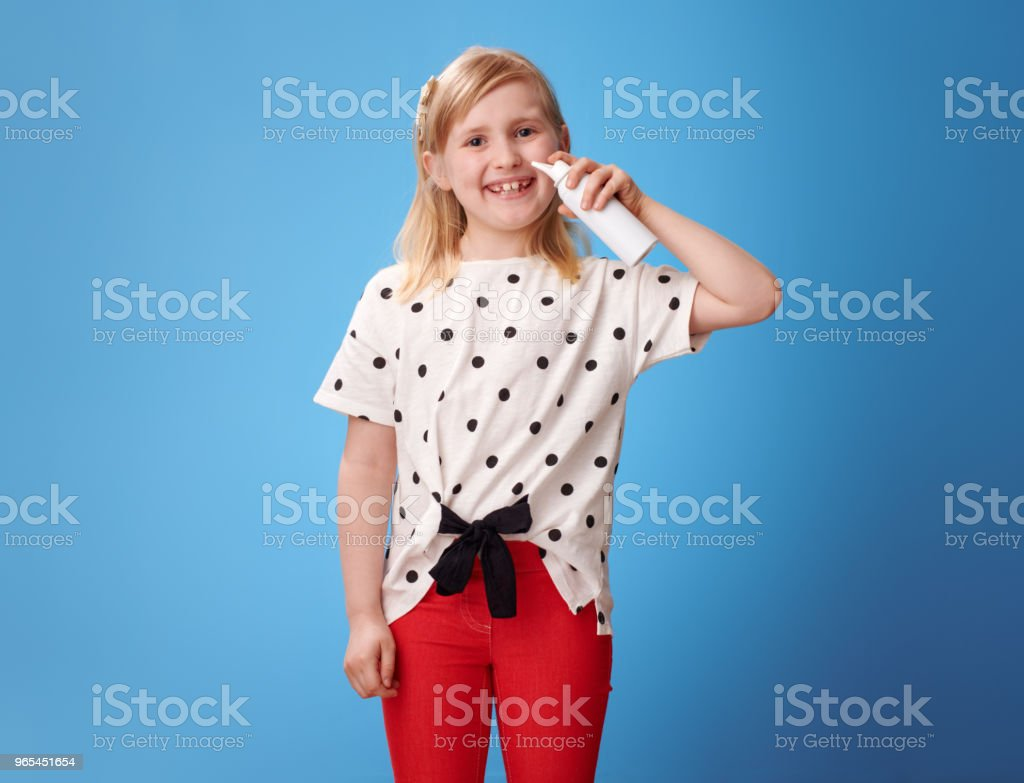 smiling modern girl using isotonic seawater nasal spray on blue royalty-free stock photo