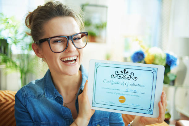 smiling modern housewife showing Certificate of Graduation stock photo