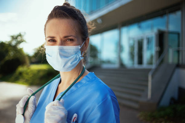 smiling modern physician woman in scrubs outdoors near clinic stock photo
