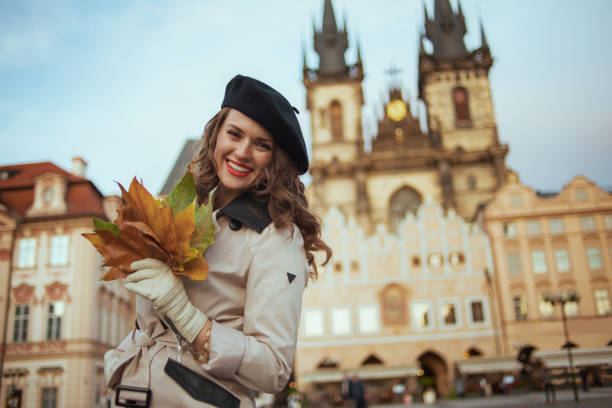 smiling modern woman in beige trench coat and black beret stock photo