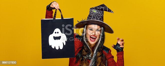 Colorful halloween. smiling modern woman in halloween witch costume isolated on yellow background showing shopping bag and frightening