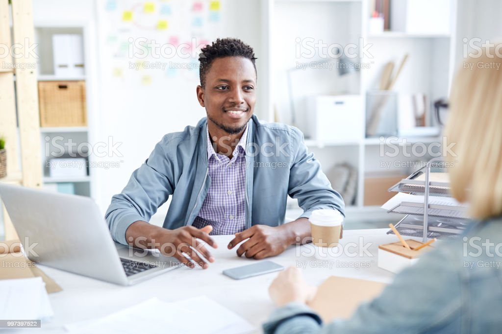 Smiling modern young black male expert in casual clothing explaining strategy to colleague while they discussing company development in office stock photo