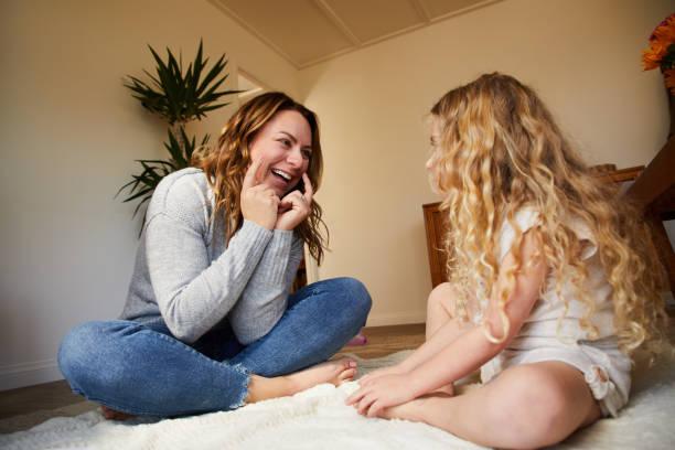 Lächelnde Mutter und ihre Tochter spielen zusammen in ihrem Wohnzimmer – Foto