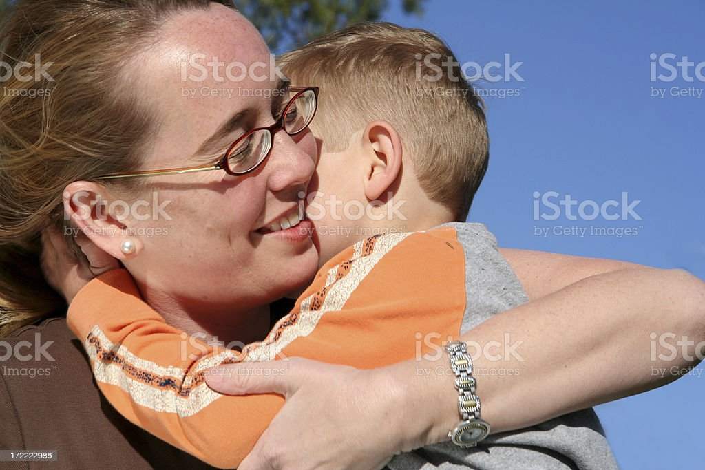 Smiling mom hugging young son outside under a clear sky. royalty-free stock photo