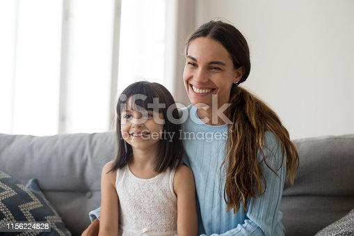 1070262182 istock photo Smiling mom with cute little daughter sit on couch talking 1156224828