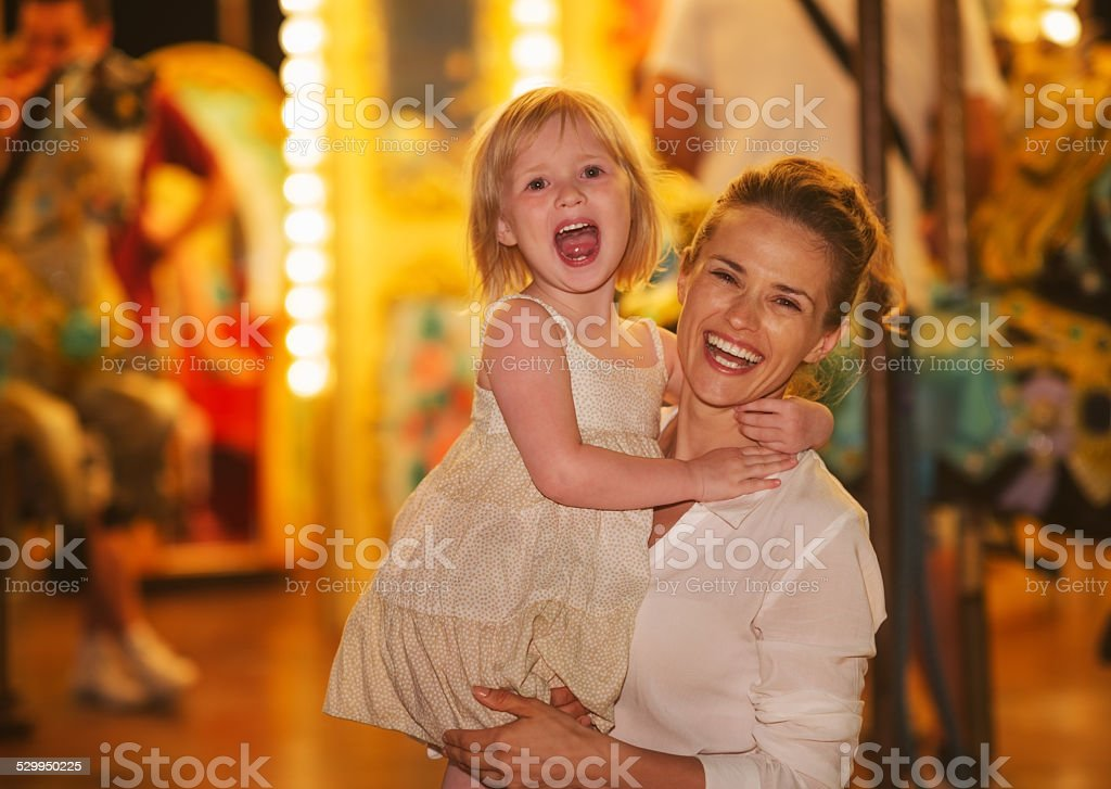 Smiling mother and baby girl in front of carousel stock photo