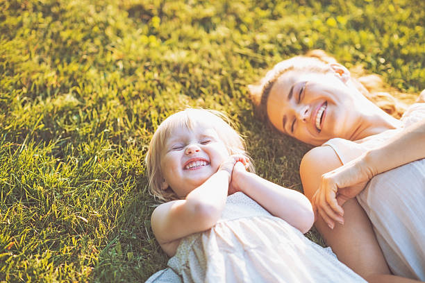 smiling mother and baby laying on meadow Smiling mother and baby laying on meadow Mother Nature stock pictures, royalty-free photos & images