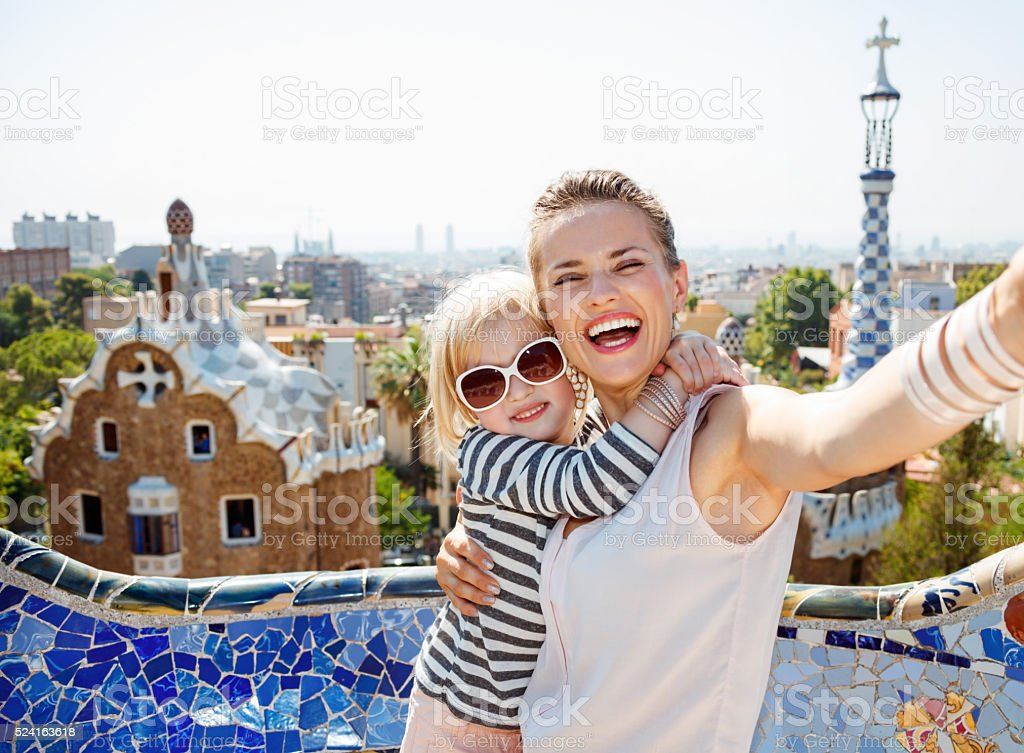 Smiling mother and baby taking selfie at Park Guell, Barcelona stock photo