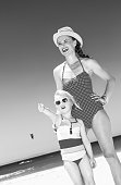 sea, white sand paradise. smiling modern mother and child in beachwear on the seashore pointing at something
