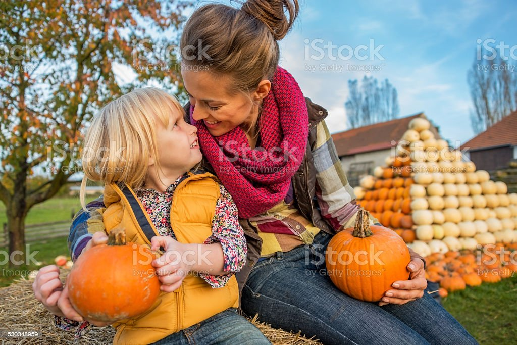smiling mother and child sitting on haystack with pumpkins stock photo