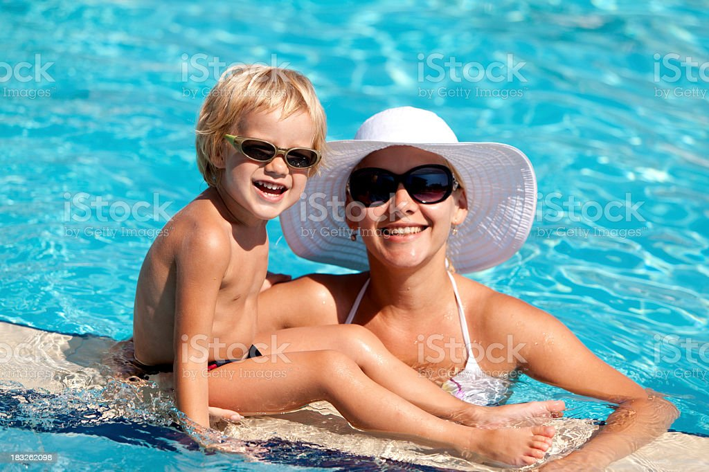 Smiling mother and child with sunglasses in the swimming pool stock photo