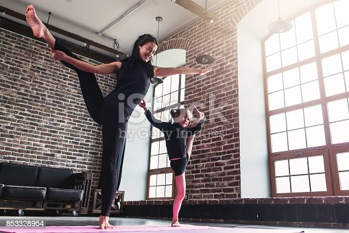 istock Smiling mother and cute little daughter in black sportswear doing standing split leg stretching exercise keeping balance 853328954