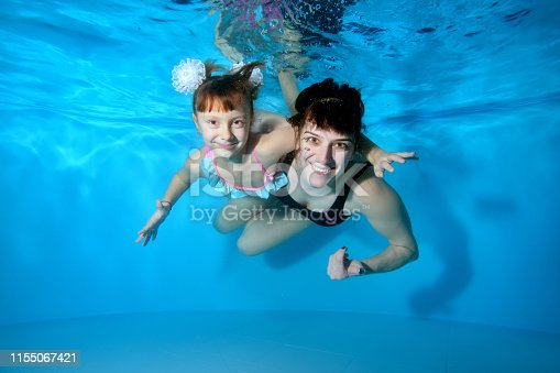 Happy little girl swimming underwater in the pool. She smiles and looks at the camera in a purple dress and swimming goggles, arms outstretched. Portrait. Horizontal view.