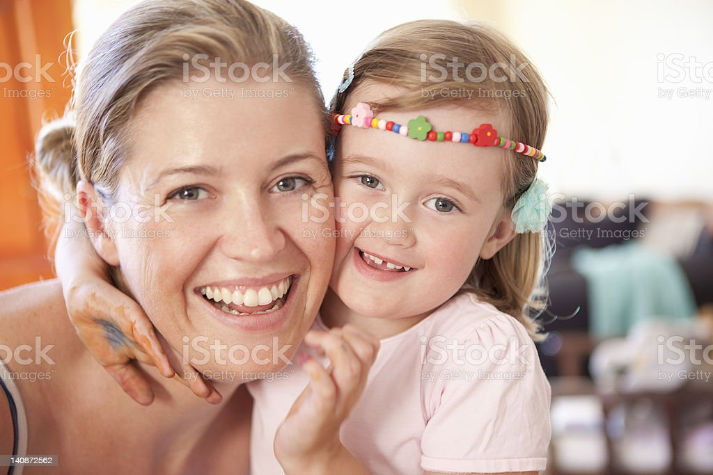 Smiling mother and daughter hugging stock photo