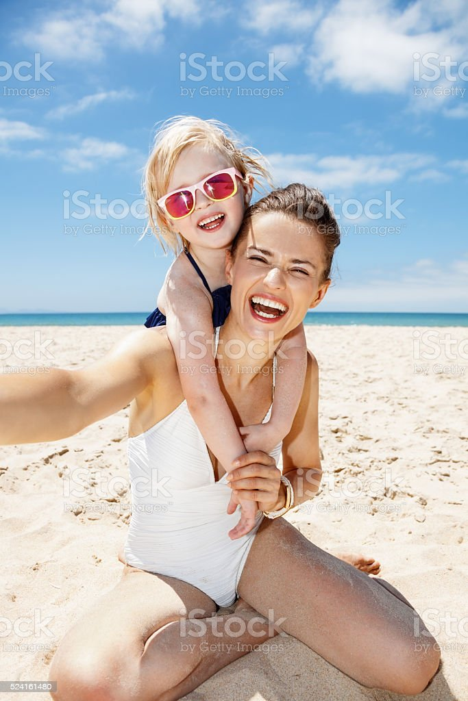 Smiling mother and daughter in swimsuits taking selfies at beach stock photo